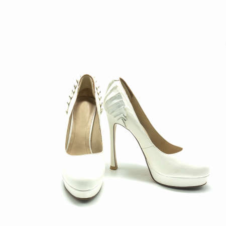 Women's white shoes with high heels and platform. Made of genuine leather. Decorated with pleats at the back. Isolated over white background.