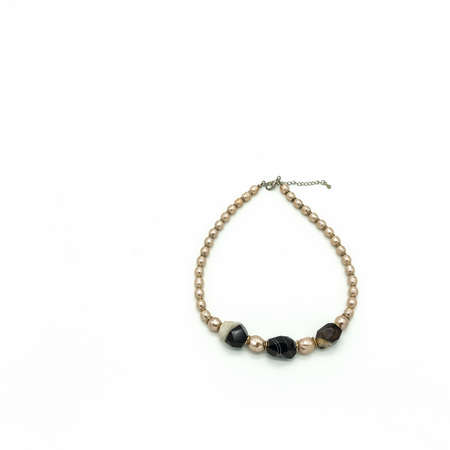 Women's bijouterie. Necklace made of pale pink and black and white beads. Metal clasp. Isolated on white background.