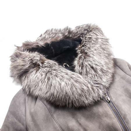 Winter women's clothing. A fragment of a gray sheepskin coat with black sheep's fur inside. Collar and hood made of fluffy silver fox fur. Metal zipper closure. White background. Bottom right corner. Foto de archivo