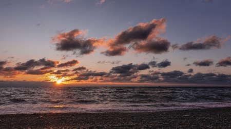 Alarming sunset over the sea. The sun is low, dusk. Purple clouds are highlighted in scarlet. At sea, waves with foam. Sunny path on the water and on the beach pebbles. Black Sea.