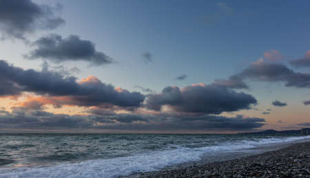 At sunset, blue clouds stand out in pink. The surf leaves an openwork white foam on the beach pebbles. The outline of the cape is visible on the horizon. Black sea Standard-Bild