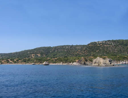 View of the coast of Cyprus from the Mediterranean Sea. A rocky coastline stretches along the calm blue water. Rocks protrude into the sea. Green vegetation on the mountain. Clear azure sky.