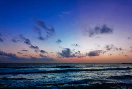 Twilight over the Indian Ocean. The sun disappeared. The sky is highlighted in pink. Blue scenic clouds. Turquoise waves roll ashore. Sri Lanka. Colombo Imagens