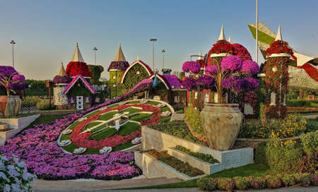 In the park there is a colorful flowerbed in the shape of a clock with a dial and hands. There are many bright colorful flower arrangements around.
