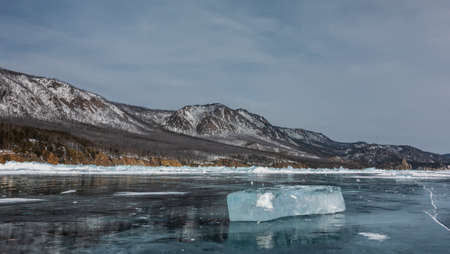 A transparent glittering ice floe lies on the frozen mirror surface of the lake. Snow-capped mountain range against the blue sky. Reflection on the surface. Baikal