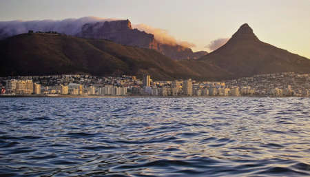 View of Cape Town from the Atlantic Ocean. The clouds on Table Mountain are illuminated by the evening sun. Lion's head rock on the background of the sky. There are many city buildings on the shore. Stock Photo