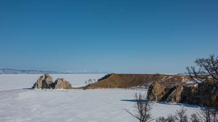 In the vastness of the frozen lake, an unusual two-headed rock, devoid of vegetation, rises. Steep rocky slopes. The ice is completely covered with snow. Clear blue sky. Baikal Stock fotó