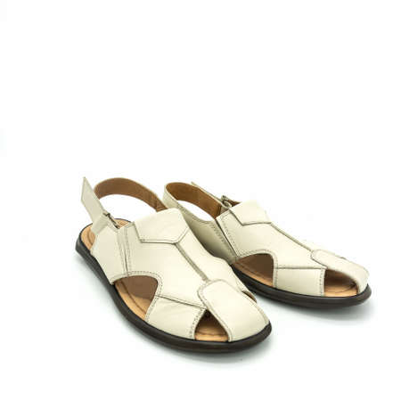 Open sandals for men made of light beige leather. Flat sole. Close-up. Isolated on white background
