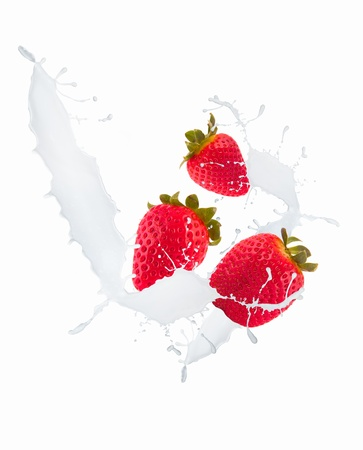 Strawberries in milk splash, isolated on white background photo