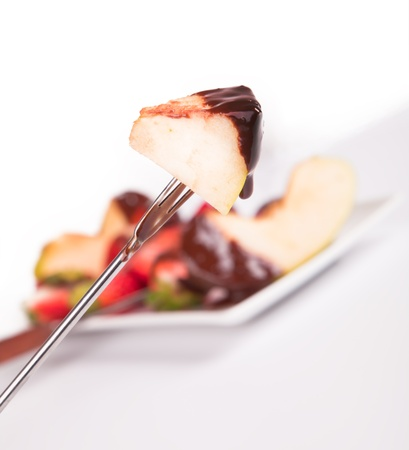 dipped: apple dipped in chocolate fondue  Stock Photo