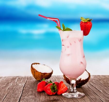 helados: Bebida del verano con la playa de desenfoque en el fondo