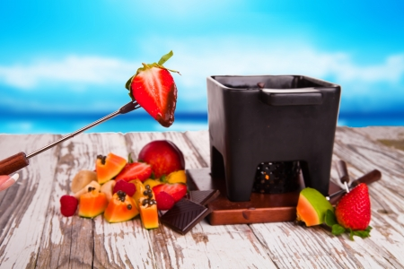 Chocolate fondue with fresh fruits on wood  photo