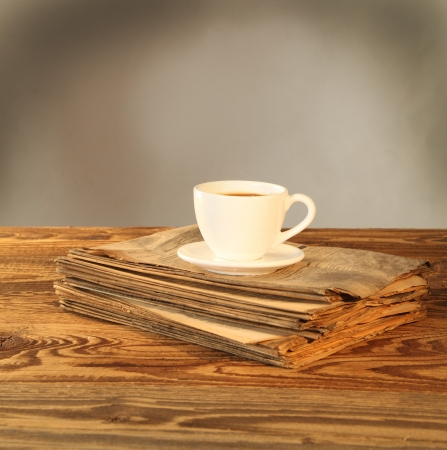 Cup of tea on newspaper on wood photo