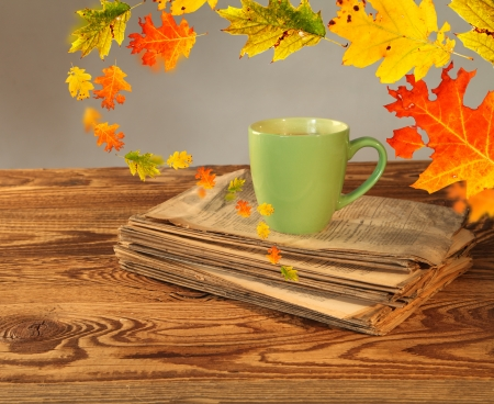 Cup of tea with autumn leaves reflection on newspaper on wood  photo
