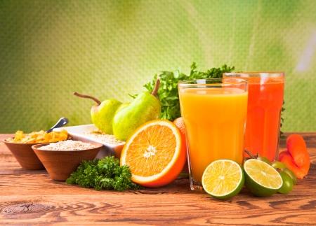 Verse groenten, fruit en sap geïsoleerd op hout Stockfoto