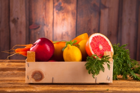 Fresh vegetable and fruits on wooden background photo