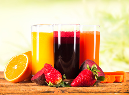 fresh juice on wooden table with nature background photo