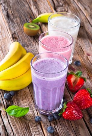 Verse melk, aardbeien, bosbessen en banaan drankjes op wodeen tafel, geassorteerde eiwit cocktails met vruchten Stockfoto
