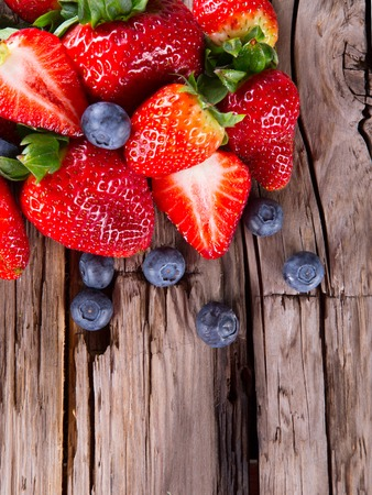 Fresh berries on wood background, strawberry and blueberry fruits, wooden table  Standard-Bild