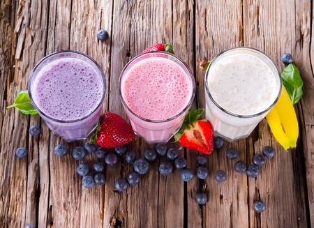 Verse melk, aardbei, bosbessen en bananadranken op wodeen tafel, geassorteerde eiwitcocktails met fruit