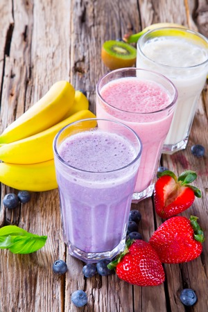 Fresh milk, strawberry, blueberry and banana drinks on wodeen table, assorted protein cocktails with fruits
