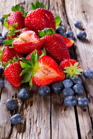 fruit bowl: Fresh strawberries and blueberry on wooden table  Garden fruits  Organi c