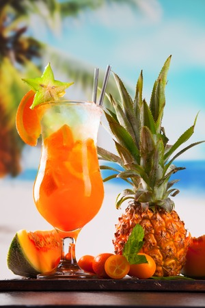 Summer drink on wooden table  Cocktail with blue sky, tropical becha and fresh fruits  photo