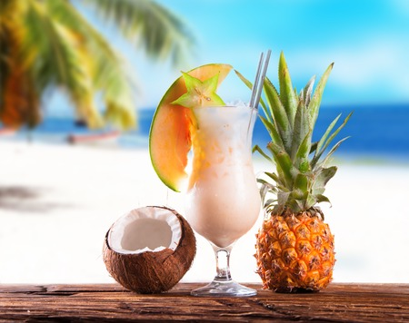 Summer drink on wooden table  Cocktail with blue sky, tropical becha and fresh fruits  Stock Photo