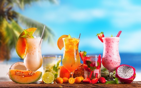 Summer drinks on wooden table  Cocktails with blue sky, tropical becha and fresh fruits  photo