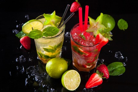 Summer strawberry and lime cocktails , drink with fresh fruits on black stone  photo