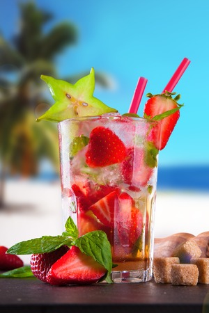 Summer strawberry cocktail , drink with fresh fruits on wooden table and tropical beach  Blue sky, sea photo