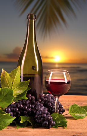 Red wine bottle with fresh grape on wooden table, tropical beach  Summer concept