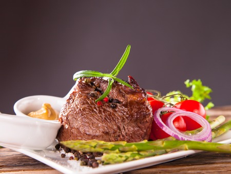 Delicious beef steaks with fresh vegetable and trimmings on wooden table