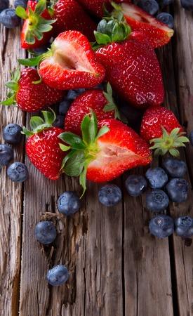 Verse bessen op houten achtergrond, aardbei en bosbessen fruit, houten tafel