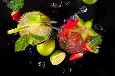 Summer strawberry and lime drinks with fresh fruits on black stone, table  photo