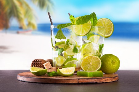 Summer lime cocktail , drink with fresh fruits on wooden table and tropical beach  Blue sky, sea photo