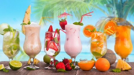 Summer drinks, juice on wooden table  Cocktails with blue sky, tropical beach and fresh fruits  photo