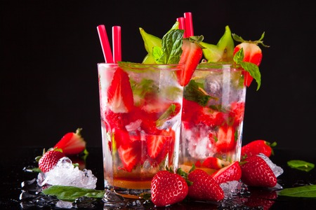 Summer strawberry drinks on black stone, table  photo
