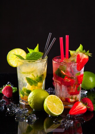 Summer drinks, lime and strawberry on black stone,table  photo