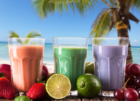 Fresh milk, grapefruit, kiwi, apple and grape drinks on wood background, assorted protein cocktails with fruits  photo
