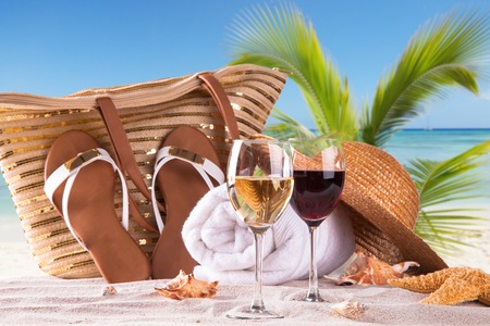 Summer concept with sandy beach, shells and wine drink