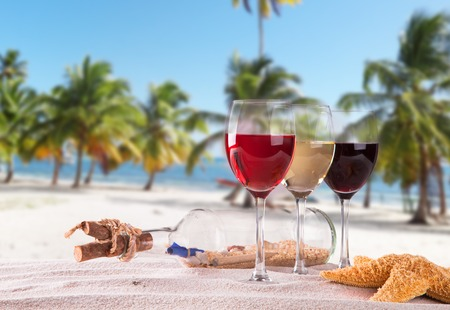 swimming candles: Wine glasses on beach Stock Photo