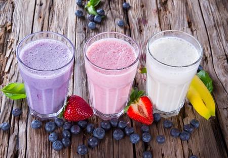 Verse melk, aardbeien, bosbessen en banaan drankjes op wodeen tafel, diverse eiwit cocktails met fruit Stockfoto