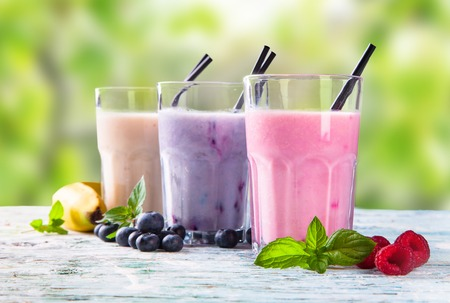 Fresh milk, strawberry, blueberry and banana drinks on wodeen table, assorted protein cocktails with fruits. Stock Photo