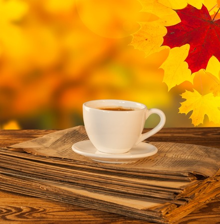 Cup of tea with autumn leaves with season vegetable on wooden table photo