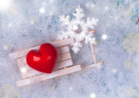 Red heart on a frosty, snow flakes white snow background. photo
