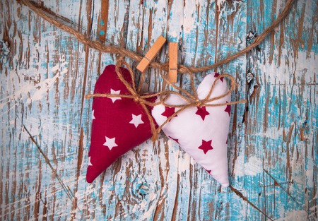 Christmas hearts hanging on wooden background photo