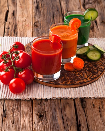 fresh juice, mix vegetable, tomato, cucumber and carrot drinks with wood plants background. photo