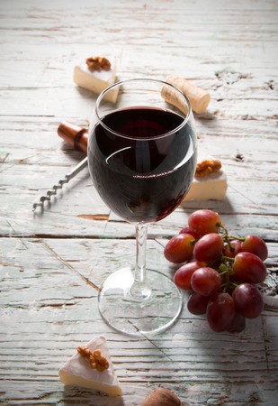 Wine and cheese on wooden table with fresh grapes photo