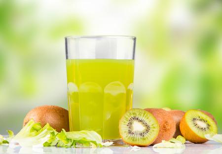 Smoothies, succo di kiwi in vetro su sfondo verde natura